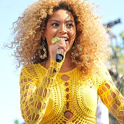 A blonde woman with dark skin, wearing a yellow dress and holding a microphone.