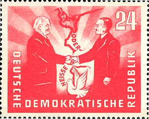 "Bolesław Bierut - 1951 East German stamp commemorative of the Treaty of Zgorzelec establishing the Oder-Neisse line as a ""border of peace"", featuring the presidents Wilhelm Pieck (GDR) and Bolesław Bierut shaking hands over the new border"