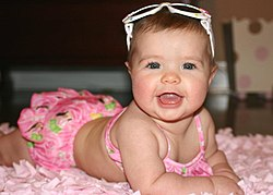 Baby girl in swimsuit blue eyes with sunglasses (23617565021).jpg