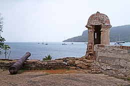 Battlements and an old cannon, overlooking a harbour.