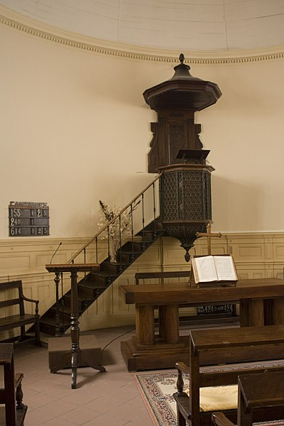 Pulpit, wood made, encased in a cast iron tub.