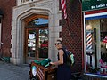 Bicycling ice cream vendor passing barbershop downstairs from where I live (35346517610).jpg