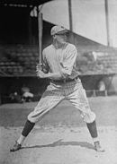 A man wearing a pinstriped old-style baseball uniform and holding a baseball bat over his shoulder