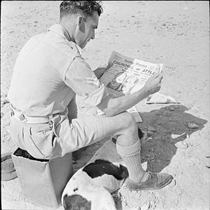 Sunday Dispatch - British Forces in the Middle East, 1945: Before voting at a tented polling station close to the pyramids, Corporal E Hopwood of 10 Maple Avenue, Acton, Wrexham, studies the Sunday Dispatch newspaper lead article on how the two main parties, Conservative and Labour, are faring in the run up to polling day (United Kingdom general election, 1945).