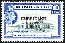 A rectangular postage stamp, denoting that the stamp is of the British Honduras and costs ten cents. In the center there is a picture of the terminal to Stanley Field Airport, with the words 'HURRICANE HATTIE' printed over it. At the bottom of the stamp reads 'Postage & Revenue'.