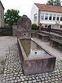 Brunnen an der Bruder-Klaus-Kirche, rechts ehemaliger Kindergarten von Niedergailbach.JPG