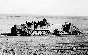 8.8 cm Flak 18/36/37/41 - North Africa, towed behind a SdKfz 7, with its side outriggers lifted for transport visible behind the gun shield