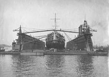Large ship atop a floating platform with two tall walls running along her side, and construction equipment between the walls and the ship