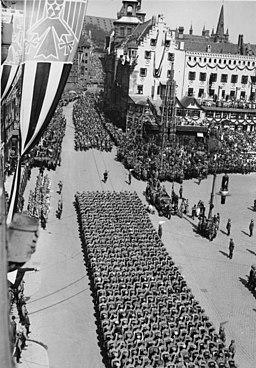 Reichsparteitag 1934 in Nürnberg: Vorbeimarsch der SA und SS Abteilungen auf dem Adolf-Hitler-Platz. Bundesarchiv, Bild 183-K0326-0503-003 / CC-BY-SA 3.0 [CC BY-SA 3.0 de (https://creativecommons.org/licenses/by-sa/3.0/de/deed.en)], via Wikimedia Commons