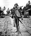 COLLECTIE TROPENMUSEUM Een man van Nias in krijgskleding met op de achtergrond een springsteen TMnr 10005457.jpg