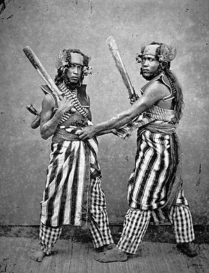 COLLECTIE TROPENMUSEUM Lombokkers in feesttenue voeren een traditionele krijgsdans uit. TMnr 60004285