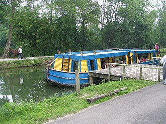 Miami and Erie Canal - Barge General Harrison of Piqua on the canal in the Piqua, Ohio, Historical Area, in July 2006. Note the captain steering the canal boat and the towing mule  on the towpath on the far side. The canal is wide enough to permit two barges to pass.