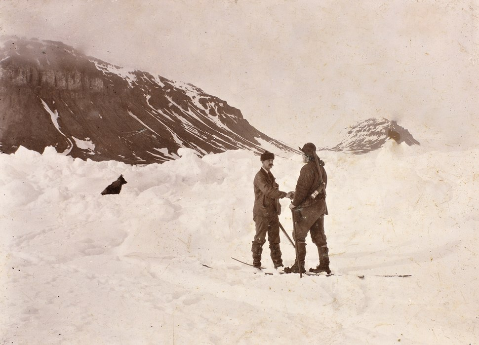 Two men shake hands in the midst of a snowfield, with a dog sitting nearby. Dark hills are shown in the background.