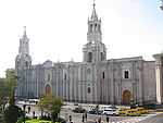 Facade of a very large white church with two tall towers.