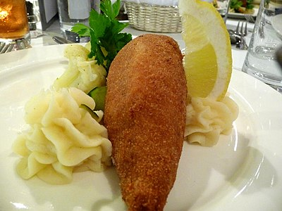 A chicken Kiev on a plate served with mashed potato and a lemon wedge