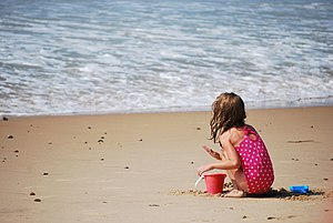 English: A female child playing in the sand at...