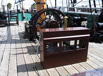 Binnacle - A compass binnacle in front of the ship's wheel. The small stove-pipe chimney vents the lamp used to illuminate the compass face at night.