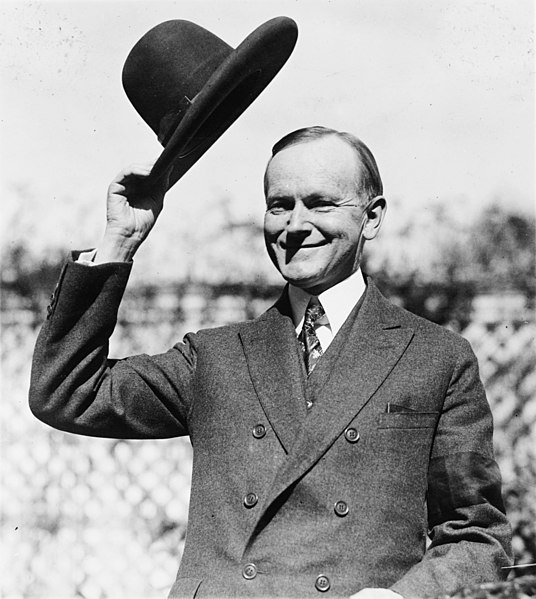 U.S. President Calvin Coolidge, half-length portrait, standing, facing left, tipping his hat.