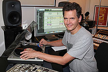 Craig Kallman holding a vinyl record at a recording workstation