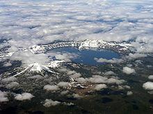 Una veduta aerea di un lago circolare circondato da pareti di roccia continue.  nuvole soffice parzialmente oscurano la vista del lago e la terra al di là.