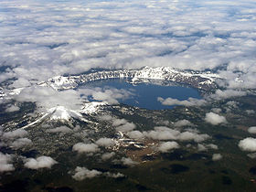 The caldera of Mount Mazama is visible, filled with the water of Crater Lake. A mountain sits to the left of the lake. Snow surrounds the lake and sits atop the nearby mountain.