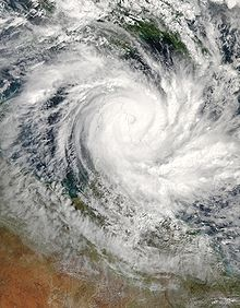 Satellite view of a large, well-developed tropical cyclone near northern Queensland. A pronounced, yet cloud-filled, eye and curved rainbands mark the characteristics of a mature storm.