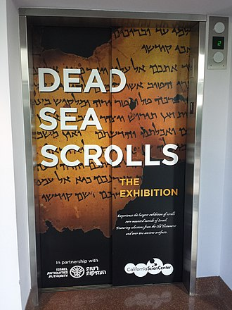 "Israel Antiquities Authority - Elevator door poster for the Dead Sea Scrolls exhibition at the California Science Center in Los Angeles. Text in the bottom left reads ""In partnership with the Israel Antiquities Authority."" The exhibit was advertised as the largest-ever exhibition of scrolls outside of Israel."