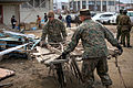 Defense.gov News Photo 110402-M-TY365-058 - U.S. Marine Corps Staff Sgt. German Estrada left and Staff Sgt. Jaime Barajasmora carry a piece of debris while helping to clean the Minato.jpg
