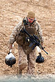 Defense.gov News Photo 120211-M-EV518-881 - U.S. Marine Corps 1st Sgt. Adam Bala hauls black tar heroin discovered during a raid on an identified insurgent weapons cache during Operation.jpg