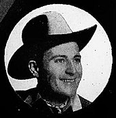 A smiling man wearing a cowboy hat