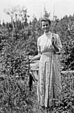 Winifred Trainor in a plaid dress, standing and facing the viewer. She is holding a string of fish in her right hand and a fly fishing rod in her left hand.