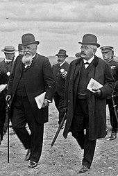 Twee mannen met hoed en vlinderdas op, met elk van de documenten onder hun linkerarm, lopen naast elkaar: de man links, met de witte snor en baard, leunt op een wandelstok;  de man rechts heeft een zwarte snor, draagt een bril en houdt een paraplu vast;  op de achtergrond zijn zes andere mannen te onderscheiden