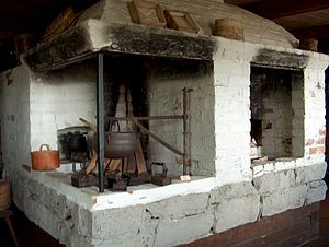 Chimney crane - A crane holds one large pot in this raised hearth fireplace in Finland