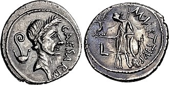Denarius of Caesar, minted just before his murder, in 44 BC. It was the first Roman coin bearing the portrait of a living person. The lituus and culullus depicted behind his head refer to his augurate and pontificate. The reverse with Venus alludes to his claimed descent from the goddess. Gaius Julius Caesar, denarius, 44 BC, RRC 480-3.jpg