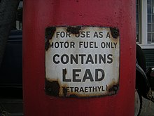 "a closeup of a red gasoline pump with a warning label that reads, ""for use as a motor fuel only"" (in larger writing) ""contains lead"" (in smaller writing) ""(tetraethyl)"""