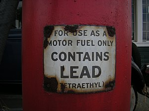 """a closeup of a red gasoline pump with a warning label that reads, """"for use as a motor fuel only"""" (in larger writing) """"contains lead"""" (in smaller writing) """"(tetraethyl)"""""""