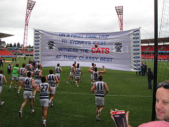 Geelong players prepare to break a banner, which is created by its supporters, before a match against Greater Western Sydney in June 2013. Geelong Cats Banner 2013.jpg