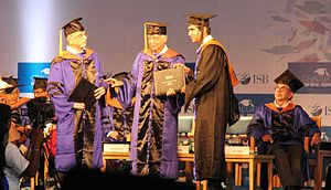 "Graduation - Student receiving academic degree from Azim Premji during a Graduation ceremony in ISB. Adi Godrej in the background. Recipient and donors in ""convocation dress""."