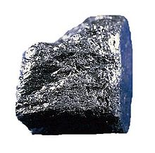 A shiny grey-black cuboid nugget with a rough surface.