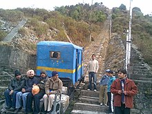 Single-car train on an incline, surrounded by people