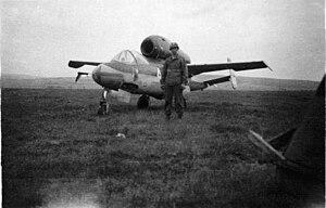 Emergency Fighter Program - American soldier guarding a captured Heinkel He 162 Spatz.
