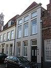 Huis onder schilddak en met gepleisterde lijstgevel waarin vensters met afgeronde bovenhoeken