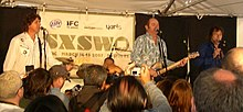 Three males at microphones partly obscured by an audience in foreground, centre male with eyes closed holds a guitar.