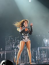 The image of a woman who is singing. She wears a black leotard and holds a microphone with her right hand while she moves quickly her left hand. Many musical instruments are visible behind her.