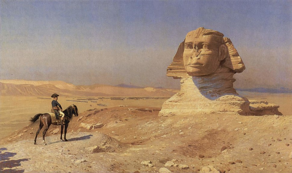 Person on a horse looks towards a giant statue of a head in the desert, with a blue sky