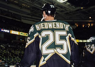 "Backside of a hockey player, looking up. He is in a black and green uniform with the name ""NIEUWENDYK"" above a large number 25 on the back."