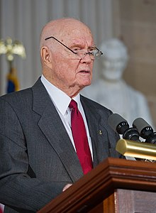 An older John Glenn speaking at a podium, with his glasses perched high above his ears so he can read with them