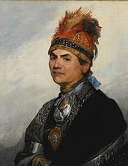 A head and shoulders oil portrait of Joseph Brant. He wears Indian garb, including a wide headband decorated with feathers and beads, a metal gorget, and a dark cape with a silver fringe.