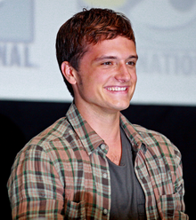 Josh Hutcherson smiling, wearing an open patterned brown and tan flannel, with a brown shirt underneath