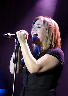 An image of an blonde haired woman, wearing a black t-shirt, singing against a dark violet background